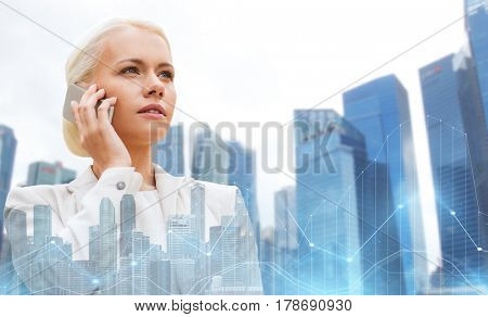 business, technology and people concept - serious businesswoman calling on smartphone over city and office buildings with charts background