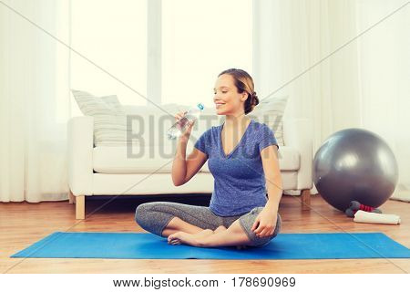 fitness, sport, people and healthy lifestyle concept - happy woman with bottle of water after exercising on mat at home