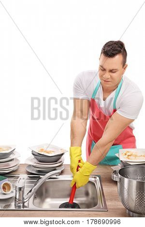 Young man unclogging a sink with a plunger isolated on white background