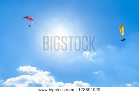 Two Paragliders Flying Against The Blue Sky With White Clouds.