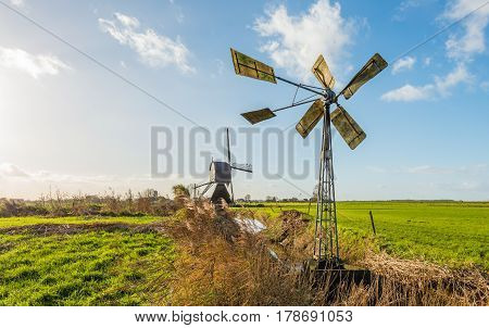 Small metal windmill and a large wooden hollow post mill in a Dutch polder landscape on a sunny day in the fall season.