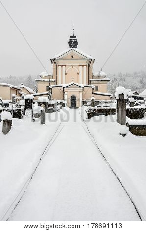 Cemetery and catholic church covered in snow in winter time. Religious graveyard with tomb stones and a church in snowy winter.