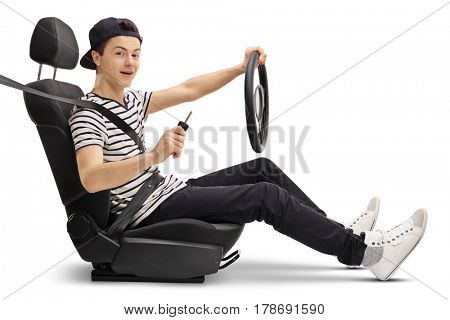 Teenager in a car seat holding a steering wheel and a car key isolated on white background