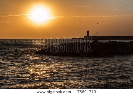 Silhouette Of Lighthouse, Reef, And Choppy Sea At Sunset
