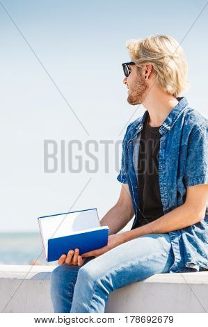 Holiday outdoor leisure time introvert relaxation concept. Sitting hipster man wearing jeans outfit having break from reading book outside on sunny day sea in background