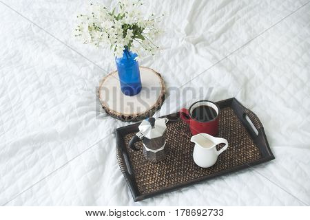 Cup of coffee with a blue vase on a wooden tray on white bed, hotel or home