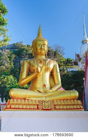 The gold buddha statue sitting on the ground.