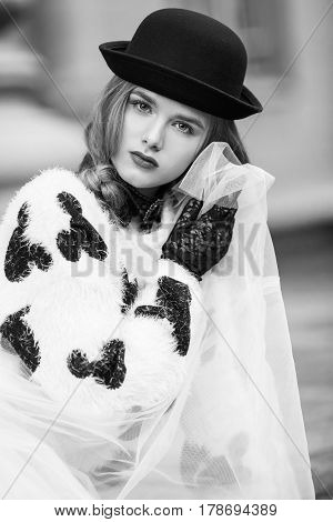 Woman in black and white clothes. Stylish retro urban girl trendy new age look. Accessories hat and Gloves. Portrait of fashion model posing in city stree.