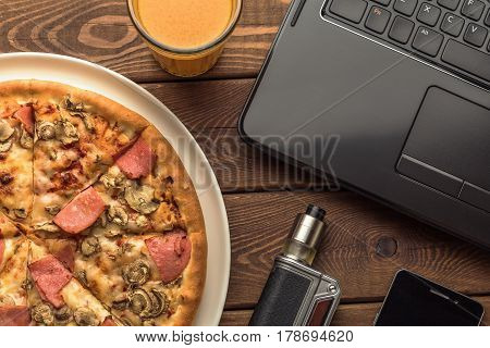 Pizza with ham and mushrooms on a plate, laptop, electronic cigarette or vape, mobile phone and a glass of sea-buckthorn fruit juice on wooden table, top view, toned photo, fast food concept