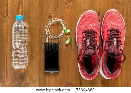 Bottle Of Water, Telephone And Running Shoes For Sports On A Dark Wooden Floor View From Above Close