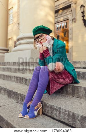 Sad student girl sitting on steps of univercity. Upset woman posing at campus of univercity. Fashion shot of young teen model in hat and glasses in trendy creative clothes