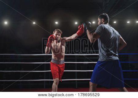 Fighting men in boxing ring