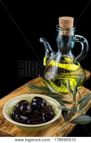 Black olives, bottle of olive oil and olive branch on wooden chopping board and black background