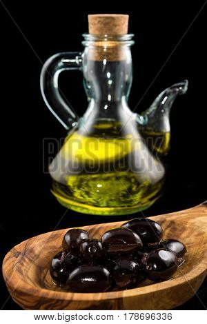 Black olives in wooden spoon and bottle of olive oil on black background