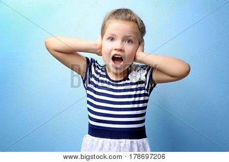Cute little girl covering ears with hands, on color background