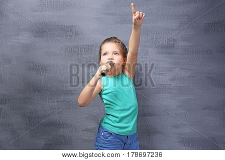 Cute little girl with microphone on color background