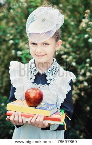 Portrait Of A Beautiful Young First-grader With Red Apple On Books In A Festive School Uniform