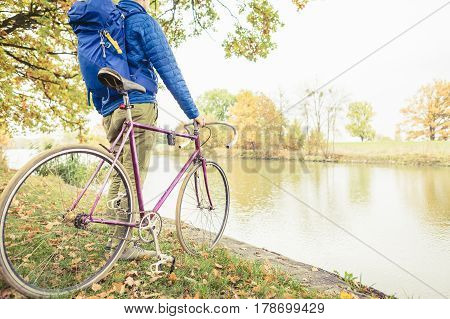 Man with road bike looking at river view in park. Male commuter and fixed gear bicycle relaxing in green park. Sport fitness motivation and inspiration in autumn nature.