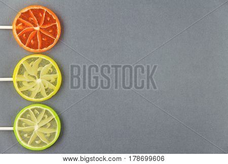 Three citrus lollipops on a gray background