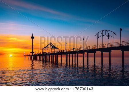People walking along Brighton Jetty at sunset. South Australia