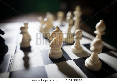 Image of the white pieces on a chess board with shallow depth of field and focus on the knight.