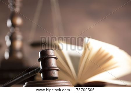 Law and justice concept - gavel of judge and scale of justice and legal code on wooden table and wooden background.