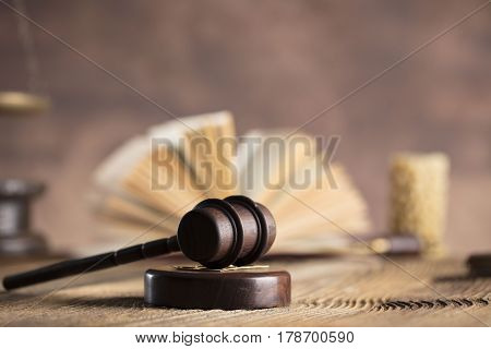 Law and justice concept - gavel of judge and legal code on glass table and wooden background.