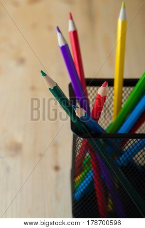 Colorful pencils on wooden table. Painting, sketching and school supplies. Crayons background with copyspace. Shallow depth of field.