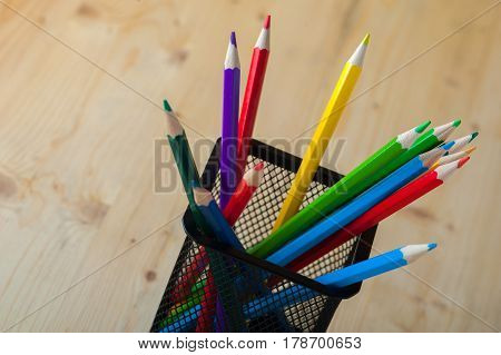 Bunch of colorful pencils on wooden table. Painting, sketching and school supplies. Shallow depth of field.