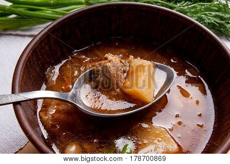 Close Up View Of Clay Plate And Spoon With Red Beetroot Soup Or Borsch On Wooden Background..