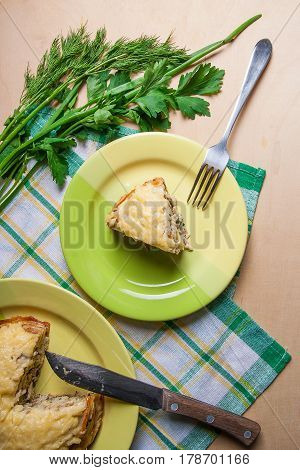 Piece Of Pancakes Pie With Mushrooms And Chicken Meat On Green Plate And Metal Fork. Traditional Mea