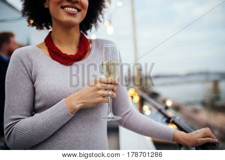 Close of afro american girl holding a glass of white wine..
