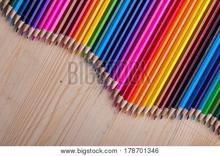 Multicolored pencils in wave form on wooden table. Bright crayons background with copyspace. Drawing and sketching supplies.