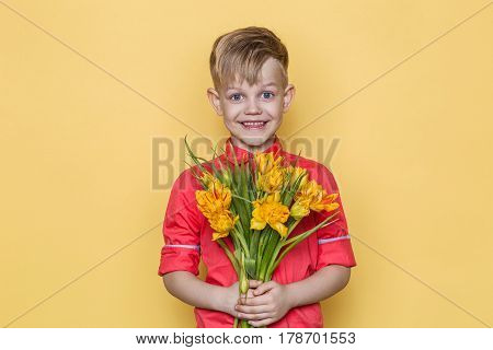 Little beautiful child with pink shirt gives a bouquet of flowers on Women's Day, Mother's Day. Birthday. Valentine's day. Spring. Summer. Studio portrait over yellow background