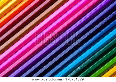 Macro view of colorful pencils. Assortment of multicolored wooden crayons. Drawing, sketching and school supplies.