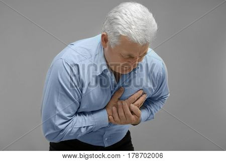 Man with chest pain suffering from heart attack on grey background