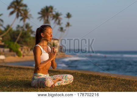 Caucasian Woman Practicing Yoga At Seashore Of Tropic Ocean At Sunset