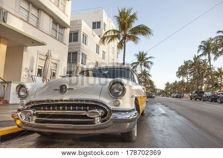 MIAMI USA - MAR 10 2017: Vintage american car parked at the famous Art Deco hotels in the Ocean Drive in Miami Beach. Florida United States