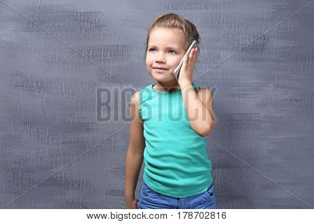 Cute little girl talking by mobile phone on color background