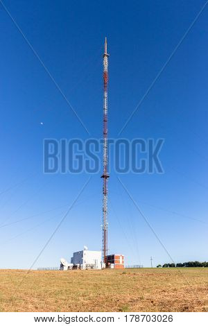 Communications signal tower tall high structureon highground hilltop for radio tv mobile phones against blue sky.
