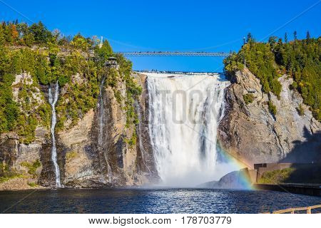 The magnificent rainbow plays in falls splashes. The concept of active and cultural tourism. The blue lake and powerful waterfall Montmorency in Montmorency Falls Park, in Quebec