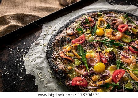 Italian pizza with black dough and seafood on a baking tray from the oven. On top of it lay squid, shrimp, octopus, onions, tomatoes. Cuttlefish ink