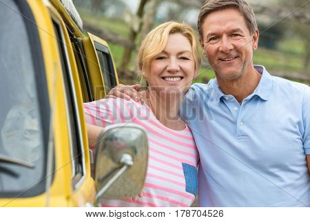 Portrait shot of an attractive, successful and happy middle aged man and woman couple together laughing by a camper van bus