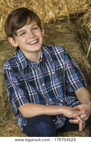 Young happy boy wearing a plaid shirt and sitting on bales of hay or straw with a toothy smile