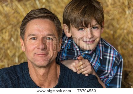 Happy father and son man and boy smiling sitting on hay or straw bales