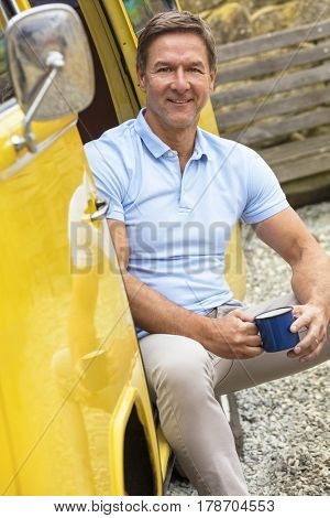 Handsome, successful and happy middle aged man sitting in the doorway of a yellow camper van bus drinking tea or coffee form a tin cup or mug