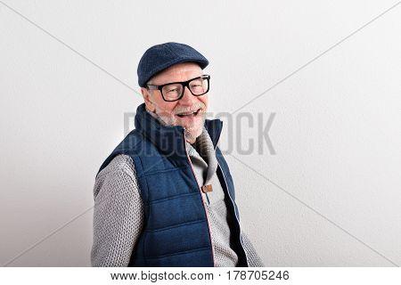 Handsome senior man in gray sweater, blue vest jacket, black eyeglasses and flat cap smiling. Studio shot against white wall.