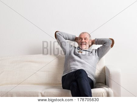 Handsome senior man in gray sweater, sitting on sofa, smiling, hands behind the head, legs crossed. Studio shot against white wall.