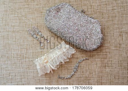Bride's garter, earrings, bracelet and a clutch with sequins are on a beige surface