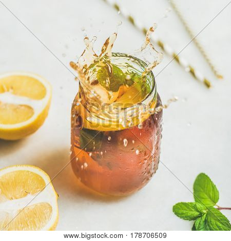 Summer cold Iced tea with fresh bergamot, mint and lemon in glass jar with splashes on light table background, square crop. Food in motion concept